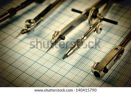 Old drawing tools on graph paper - stock photo