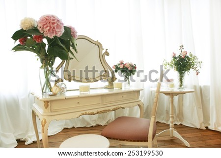 old dressing table decorated with flowers and chair - stock photo