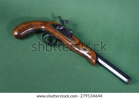 Old duel pistol on green background - stock photo