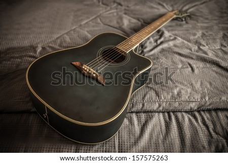 Old dusty acoustic cutaway guitar in bed in a darken bedroom
