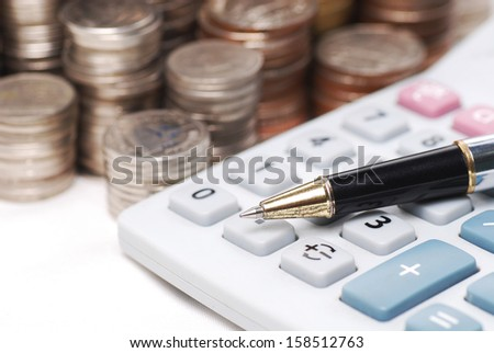 Old dusty ball pen on calculator with stack coins background