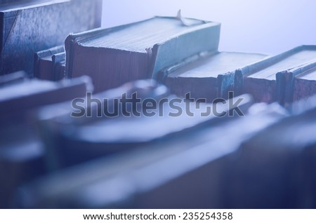 Old dusty books at night backlit - stock photo