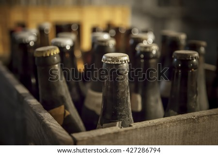 Old dusty bottle of beer in a wooden case