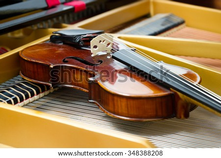 Old dusty violin laying on the grand piano strings inside - stock photo
