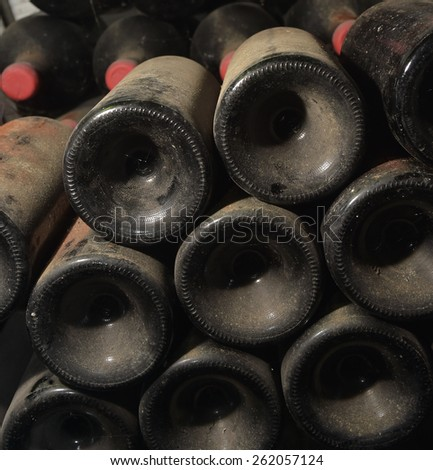 Old dusty wine bottles rest in a cellar
