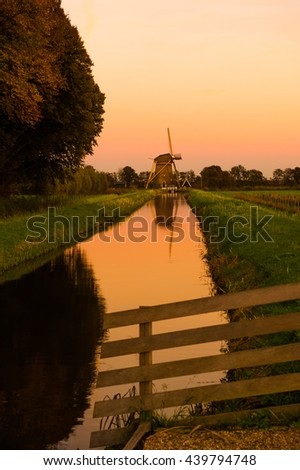 Old dutch windmill behind a fence during a beautiful orange sunset - stock photo