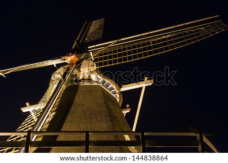 Old Dutch windmill illuminated in the dark - stock photo
