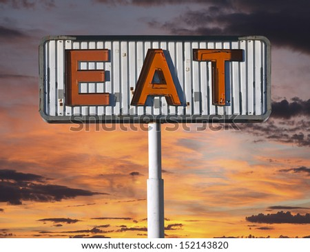 Old eat sign with sunset sky. - stock photo