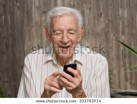 Old elder senior man on mobile smart phone - stock photo