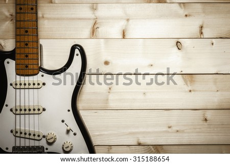 Old electric guitar on the wood background with space