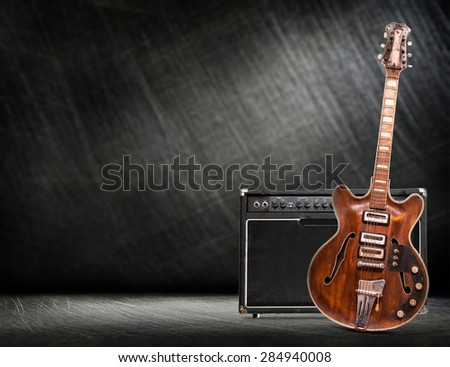 Old electric guitar vertical on steel scratchy background - stock photo