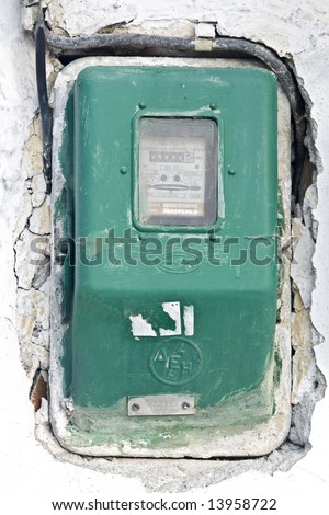 Old electric meter on a wall - stock photo