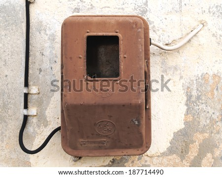 Old electric meter on grungy aged wall - stock photo