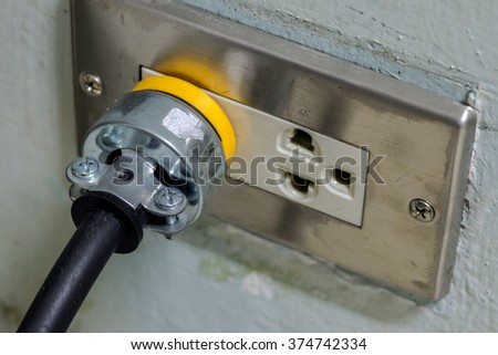 old electric Plug and outlet on cement wall - stock photo