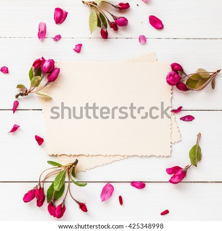 Old empty photo for the inside and frame of apple flowers on white wooden background. Flat lay, top view. - stock photo