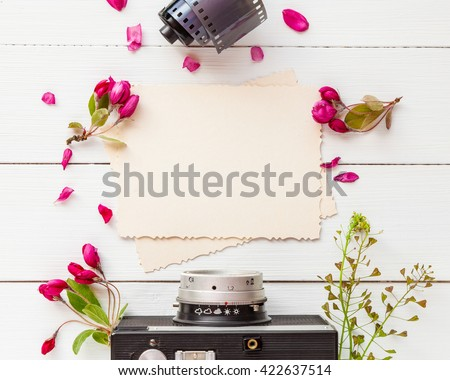 Old empty photo frame for the inside, retro camera, photo film rolls and apple flowers on white background. Flat lay, top view. - stock photo