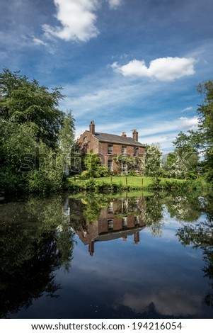 Old English farmhouse with large duck pond in the foreground creating a reflection. - stock photo