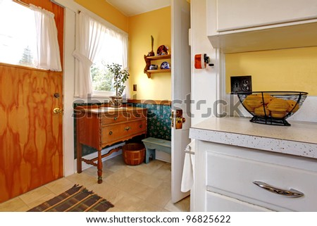 Old English kitchen with two doors and counter. Yellow and green.