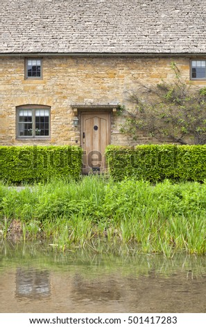 Old English stone house with light brown wooden doors, green leafy hedge, in front of river, in rural village