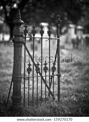 Old entrance gate and graves in an ancient church graveyard - stock photo