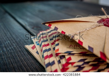 Old envelopes with a wax magic witch stamp on wooden table - stock photo