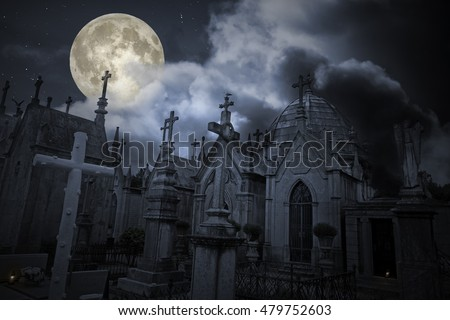 Old european cemetery in a cloudy full moon night