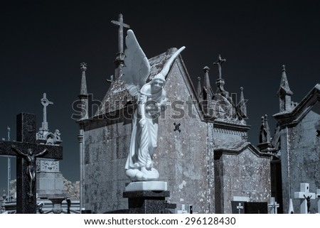 Old european cemetery with a white marble angel in the foreground. Used infrared filter. - stock photo