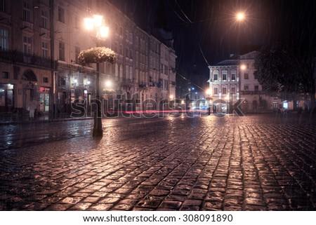 Old European city at rainy night - stock photo