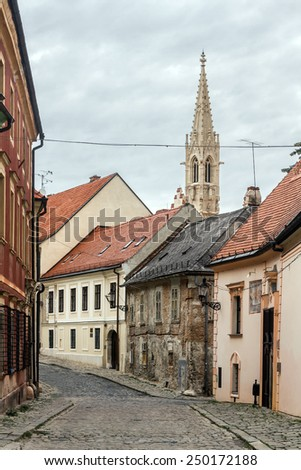 Old European small street among historic buildings with red roofs in the center of Bratislava, Slovakia. Gothic tower on the background of the cloudy sky. The street is covered with paving stones - stock photo