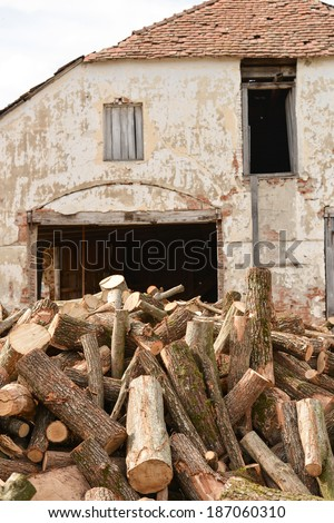 Old facade of a building ruined with stack of trunk tree near her - stock photo