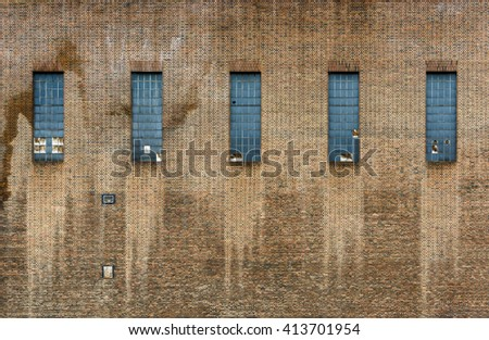 Old factory brick wall, five windows, some of them broken - stock photo