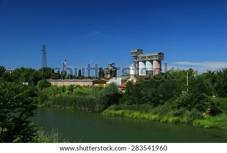 Old factory with silo tanks for corn near river - stock photo