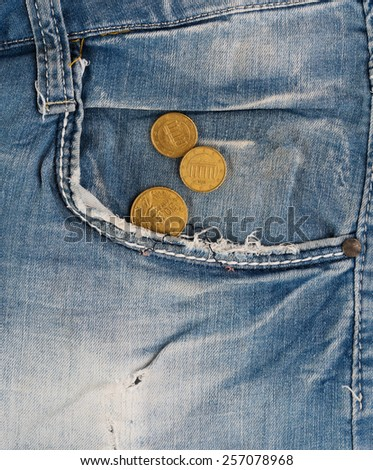 Old faded jeans with euro coins in pocket - stock photo