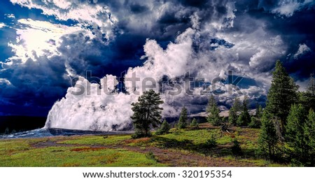 Old Faithful geyser and stormy cloud sunset. Panoramic landscape.  Wyoming, USA - stock photo