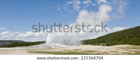 Old Faithful Geyser erupting at Yellowstone  National Park, Wyoming - stock photo