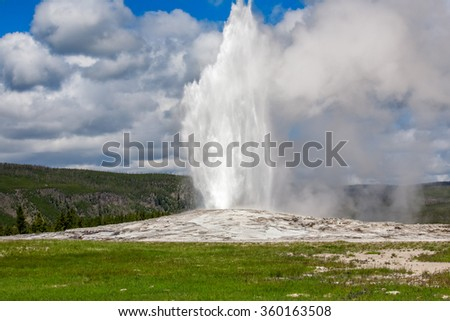 Old Faithful Geyser in Yellowstone National Park erupting - stock photo