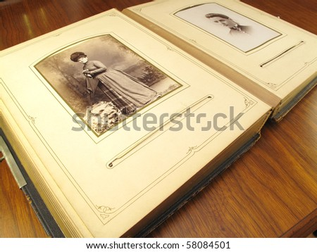Old family album opened to a page of photos - stock photo