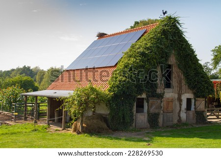 old farm house with solar panels on the roof - stock photo