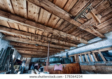 old farm storage room with junk and wooden ceiling - stock photo