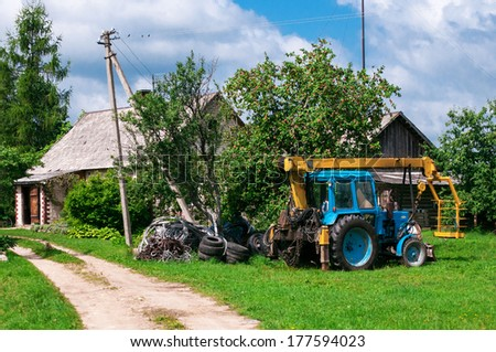 Old farm tractor stands in  village nearby  house