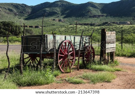 Old farm wagon made of wooden boards and with steel-rimmed wooden spoke wheels stands outside an old fence/Wild West Freight Wagon/Vintage freight wagon made of boards and steel - stock photo