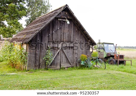 old farm wooden building and broken tractor in the village
