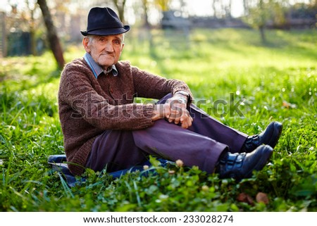 Old farmer sitting in grass at sunset - stock photo