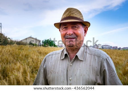 Old farmer smiling to the camera  - stock photo
