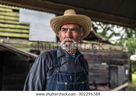 Old farmer standing in front of a rustic dilapidated wooden barn staring thoughtfully off to the side - stock photo