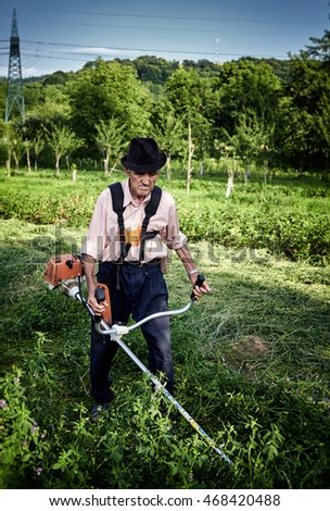 Old farmer using a petrol brush cutter to mow long grass and flowers.