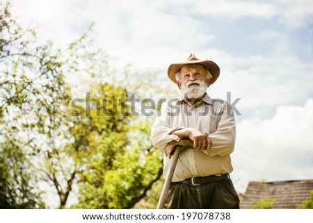 Old farmer with a hoe is having break from weeding - stock photo