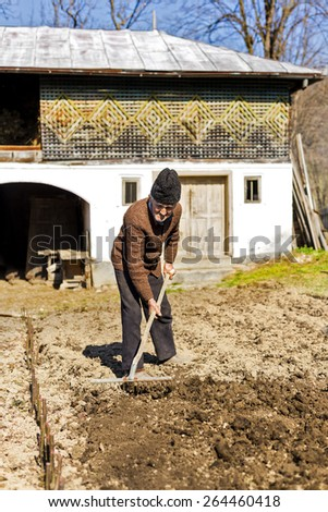 Old farmer with rake working in his garden - stock photo