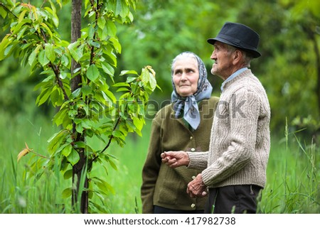 Old farmers couple looking at the trees in their orchard - stock photo