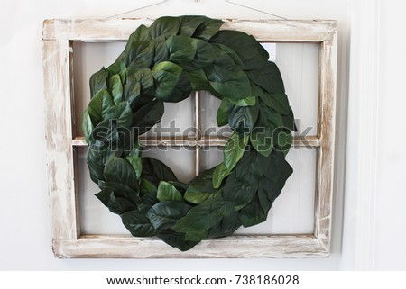 Old farmhouse window decorated with a homemade Magnolia leaf wreath hung on an interior wall.